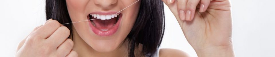 Young attractive woman with dental floss